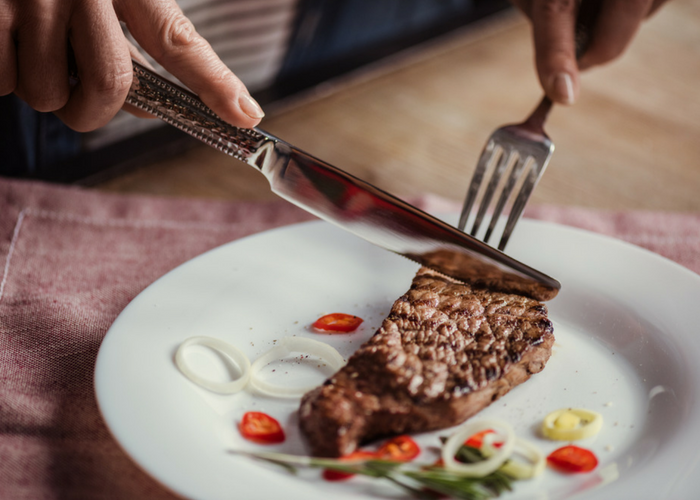 woman cutting into a piece of steak