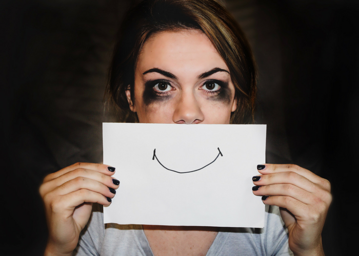 woman with black smudged eyes holding up a piece of paper to her face with a smile drawn on it