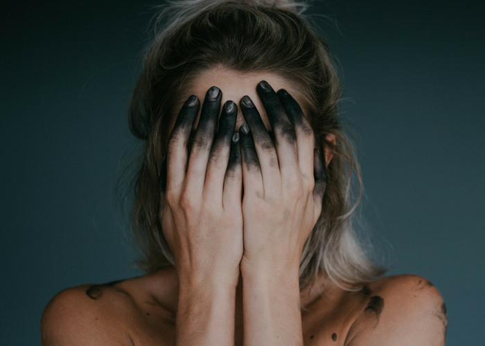 woman covering her face with with blackened fingers
