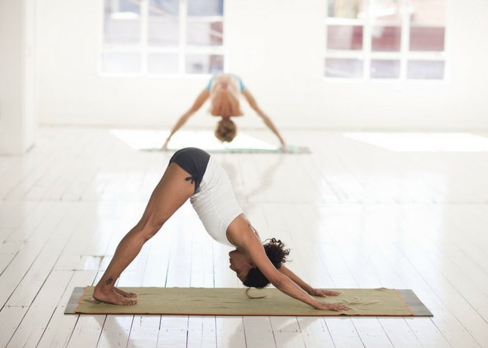 woman on yoga mat in downward dog position