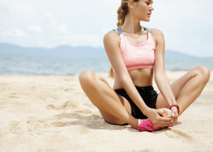 woman in fitness gear on the beach doing butterfly stretches