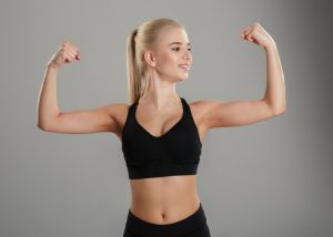 blonde woman in black sports bra flexing her biceps