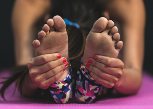 closeup of a woman stretching holding her feet