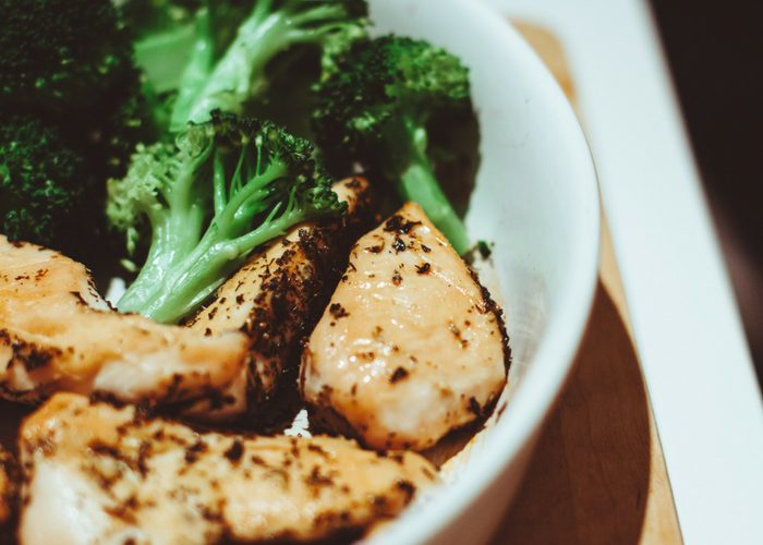 a white bowl with chicken and broccoli
