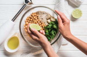 Woman squeezing lime into a bowl of vegan hummus ingredients with a blender by the side