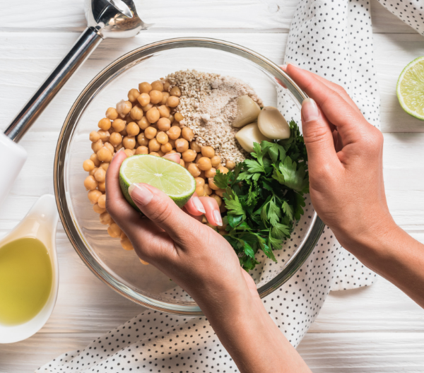 lady squeezing lime into a bowl of vegan hummus ingredients with a blender by the side