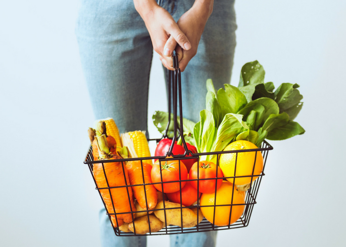 woman holding a shopping basket filled with fresh vegetables
