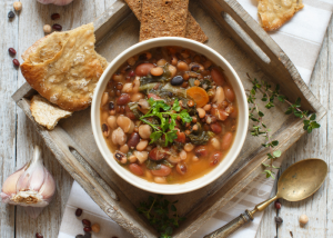 a bowl of vegan bean stew on a wooden tray
