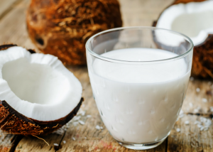 a glass of coconut milk and fresh coconut around it