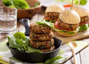 stacked vegan lentil burger patties with vegan burgers in the background