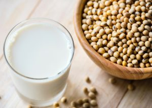 a glass of soy milk next to a bowl of soy beans