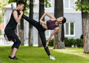 woman in a park with her fitness trainer doing leg exercises