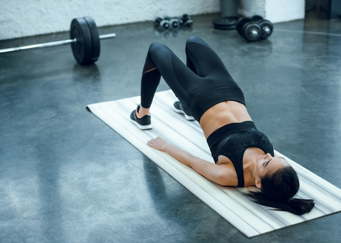 woman lying on an exercise mat with her pelvis raised doing bridges for leg exercise