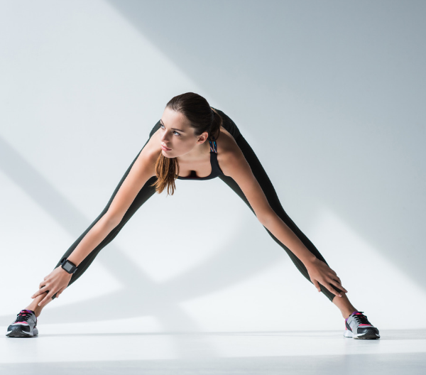 woman doing leg exercises with her body bent forward, legs wide apart and both hands reaching down to her ankles