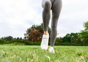 woman's legs with grey fitness leggings and white sneakers on green grass
