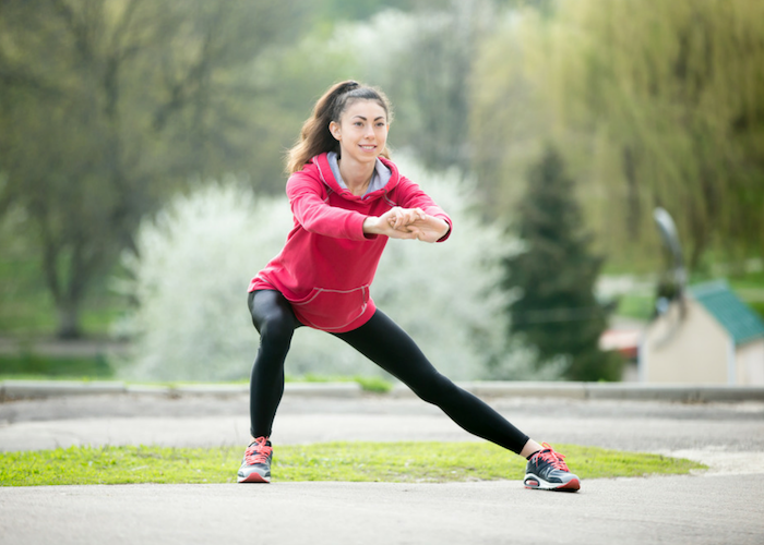 woman doing side lunges for leg exercise in an outdoor park