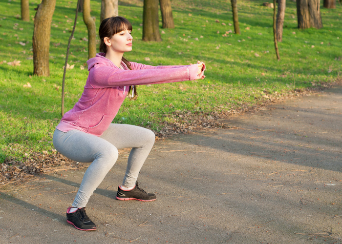 woman doing simple squats in a park