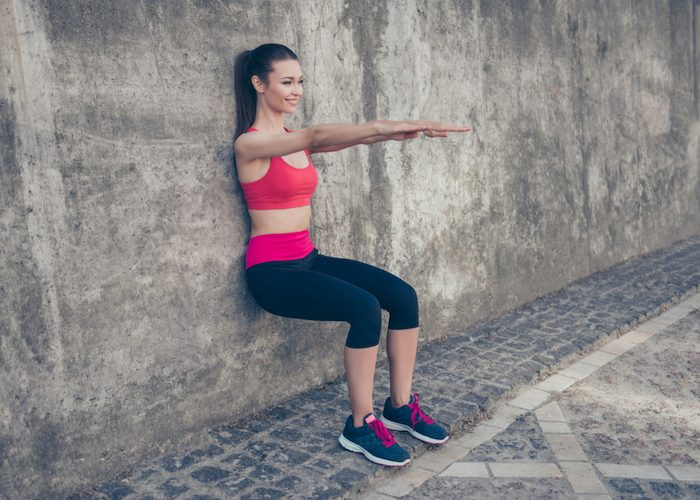 woman smiling doing wall sits outdoors