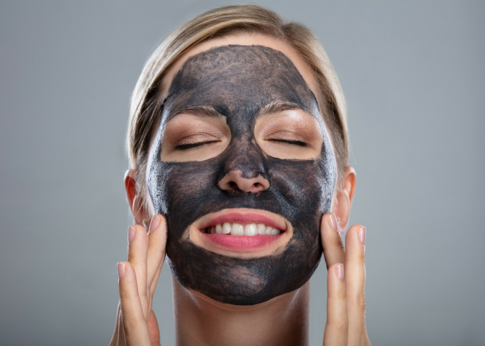 smiling woman using an activated charcoal cleanser in her best skin care routine