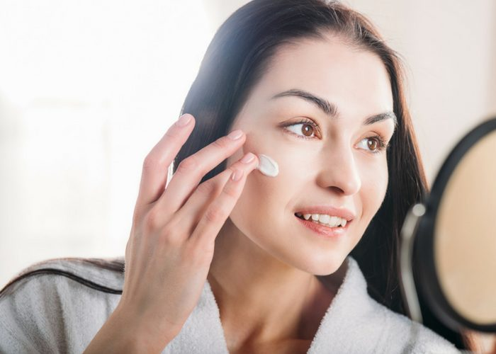 woman looking into a mirror applying barrier cream as part of her best skin care routine