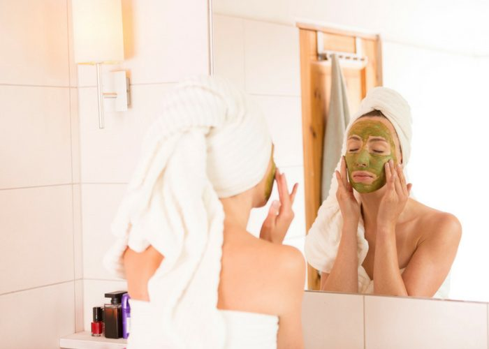 woman with a towel wrapped around her body and head applying a green tea extract face mask as part of her skin care regimen