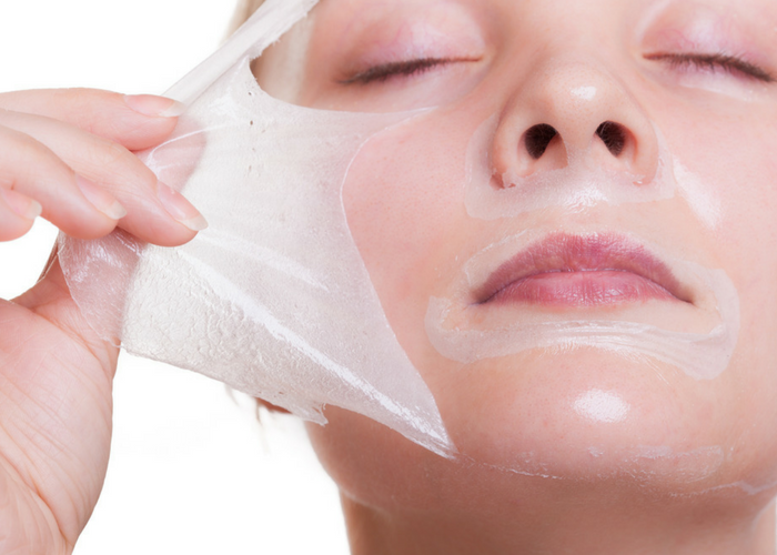 woman peeling off a hydrating face mask during her skin care routine