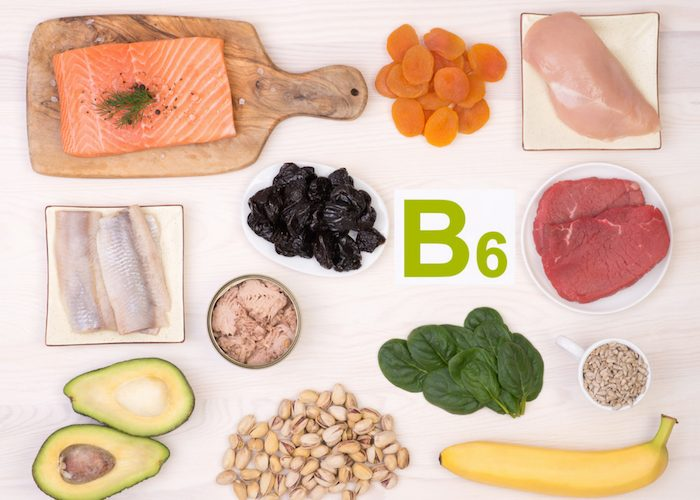 vitamin b6-rich foods such as salmon, apricots, chicken, avocado, banana, and spinach laid out on a table