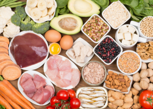 table filled with biotin-rich foods such as avocado, eggs, nuts, liver, broccoli