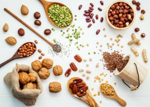 foods rich in vitamin e such as nuts and seeds on a white background