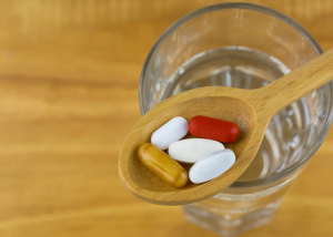 natural vitamin supplements in a wooden spoon above a glass of water