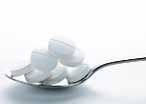 white calcium supplement tablets on a silver spoon