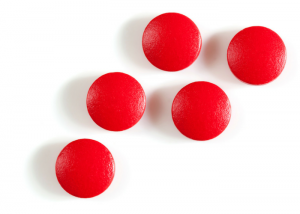 red iron supplement tablets on a white background
