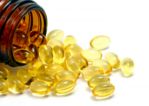 natural vitamin supplement capsules spilling out of a brown bottle