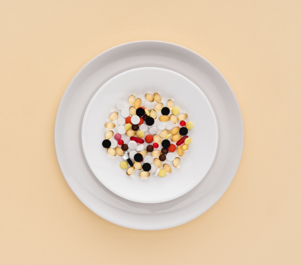 different colored supplement pills on a white dish, on top of a larger white plate, set against an eggshell yellow background