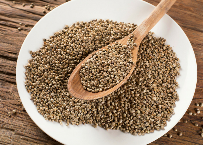 whole hemp seeds and wooden spoon on a white plate