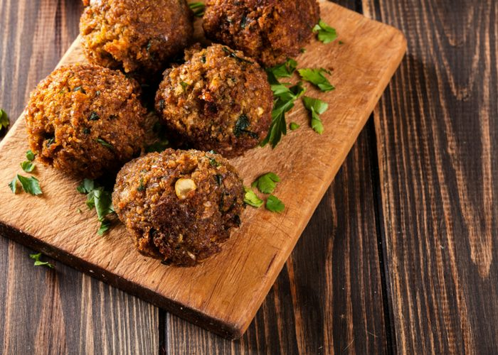 hemp seed falafel balls sprinkled with parsley served on a wooden board