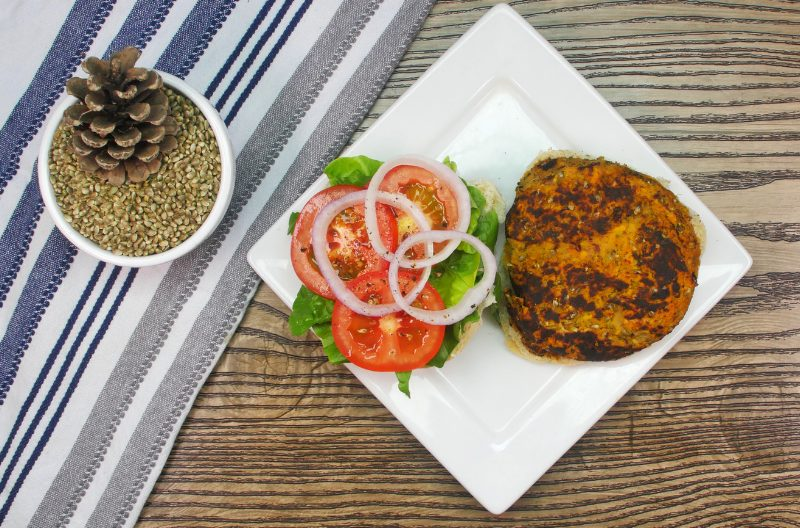 Hemp seed burger patty and vegetables on a white plate