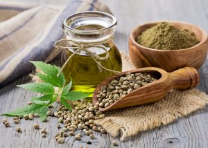hemp seed oil in a jar, ground hemp in a bowl, and hemp seeds in a wooden scoop