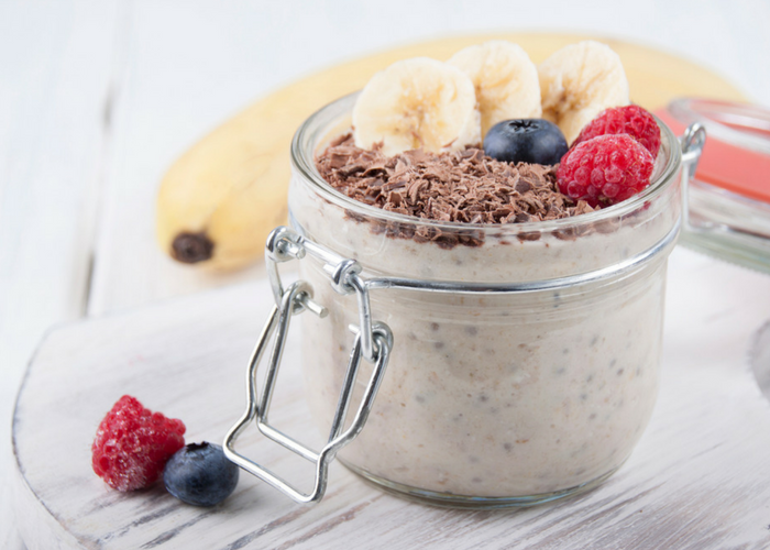 a jar of chia and hemp overnight oats topped with bananas, chocolate flakes, blueberries, and raspberries