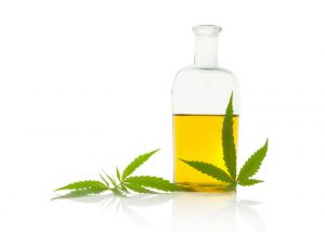 hemp seed oil in a clear bottle with two marijuana leaves beside it