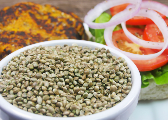 hemp seeds in a bowl with hemp seed burger patty and vegetables in the background
