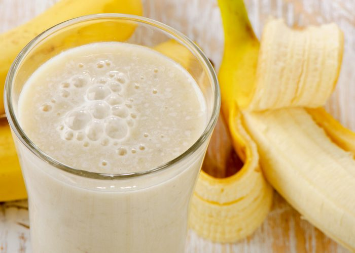 a glass of banana homemade energy drink with fresh bananas in the background