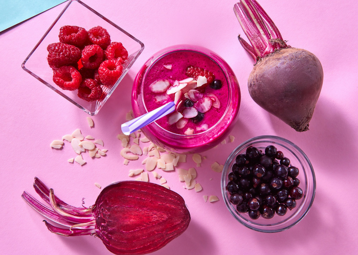 a glass of beet and berry juice topped with almonds, a cup filled with raspberries and blueberries and fresh beets around it