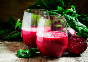 two glasses of red beet juice and the cross section of a fresh beet beside them