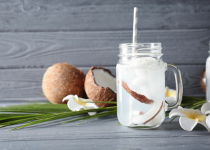 coconut water in a clear mason jar with fresh coconut pieces in it and a grey straw