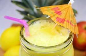 Bright yellow homemade energy drink in a mason jar with a tropical umbrella and pink straw