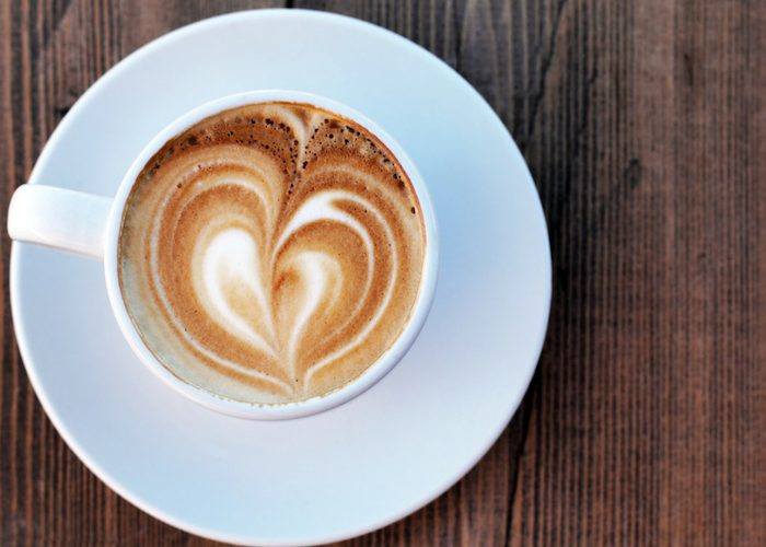 top down view of a cup of cappuccino with latte art on a wooden table