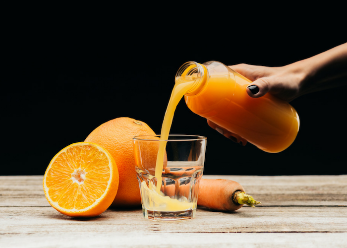 woman pouring freshly made orange homemade energy drink from a glass bottle into a glass