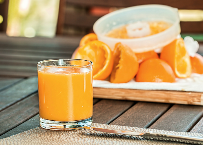 a freshly squeezed glass of orange juice and the orange peels behind it