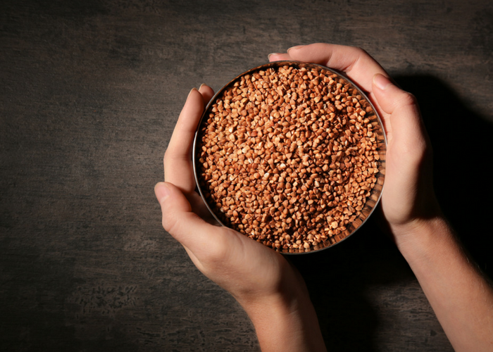 a person holding a bowl full of buckwheat grains